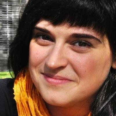 Photo du visage : jeune femme, cheveux noirs, regard souriant.